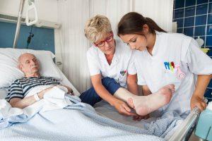 Verpleegkundige geeft instructie aan een leerling verpleegkundige.
